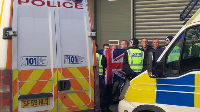 Police hold loyalist protesters back as Republican march passes