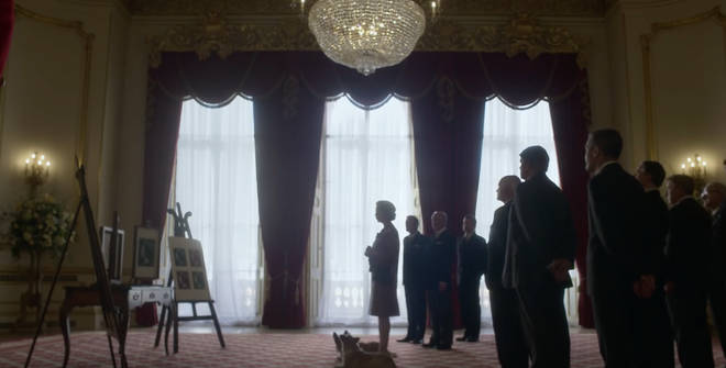 The trailer shows the Queen enter a large room full of staff