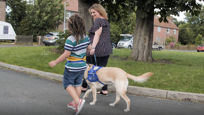 Kelly and Louis, on a walk with assistance dog Iggy