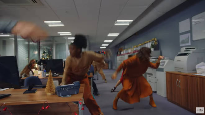 The ad features office workers dancing in various M&S jumpers