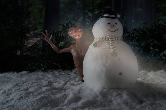 E.T. emerges from behind a snowman